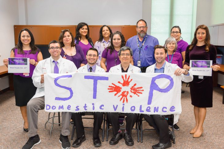 With colorful banners and signs in some of their hands, staff members at the Harlingen VA Outpatient Clinic pose for a group photo while wearing various purple garments on October 10, 2018. The staff wore purple during the month of October in observance of this year's Domestic Violence Awareness Month.