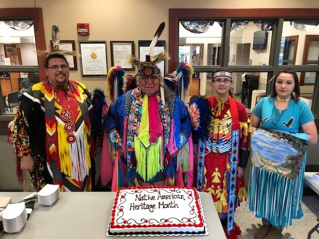 Members of the Lipan Apache Tribe of Texas pose for a group photo behind a cake with the words Native American Heritage Month decorated on it. The cake was generously provided courtesy of the VA Voluntary Service. The group of American Indian performers were the primary attraction for a special event held at the VA outpatient clinic in Harlingen, Texas, held on November 16, 2018, in observance of National Native American Heritage Month, which is officially supported by the VA's Office of Diversity and Inclusion. (Photo by Mitchell Hanks)