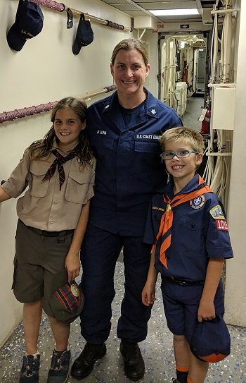 IMAGE: Coast Guard Commander Sara DiLuna poses with her children after she gave their Cub Scout pack a tour of USCGC Stratton.