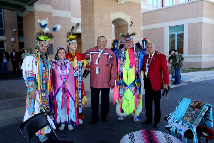(At center) Master of ceremony, Gregorio Kishketon, and Abel Flores, co-event coordinator, take a group photo with members of the Lipan Apache Tribe of Texas before the start of a special event held in observance of National Native American Heritage Month, which took place at the VA outpatient clinic in Harlingen, Texas, on November 16, 2018. (U.S. Department of Veterans Affairs photo by Luis H. Loza Gutierrez)