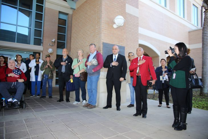 (At right) Valley Morning Star reporter Alana Hernandez takes photos while VA employees, and guests place their right hands over the left side of their chest (where the heart is located) in order to take part in reciting the pledge of allegiance to the flag of the United States of America during a special event held in observance of National Native American Heritage Month, which took place at the VA outpatient clinic in Harlingen, Texas, on November 16, 2018. At one point in time there were approximately 100 people gathered in and around the entrance to watch the performances by the Lipan Apache tribe of Texas. (U.S. Department of Veterans Affairs photo by Luis H. Loza Gutierrez)