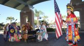A young male member of the Lipan Apache Tribe of Texas raises the U.S. flag while other tribe members play and sing in a drum circle during a special event held in observance of National Native American Heritage Month, which took place at the VA outpatient clinic in Harlingen, Texas, on November 16, 2018. (U.S. Department of Veterans Affairs photo by Luis H. Loza Gutierrez)