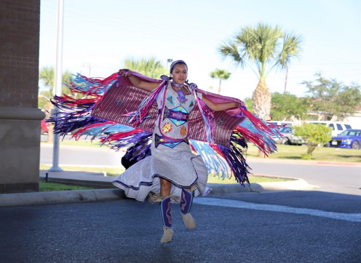 A young female member of the Lipan Apache Tribe of Texas dances while other tribe members play and sing in a drum circle during a special event held in observance of National Native American Heritage Month, which took place at the VA outpatient clinic in Harlingen, Texas, on November 16, 2018. (U.S. Department of Veterans Affairs photo by Luis H. Loza Gutierrez)