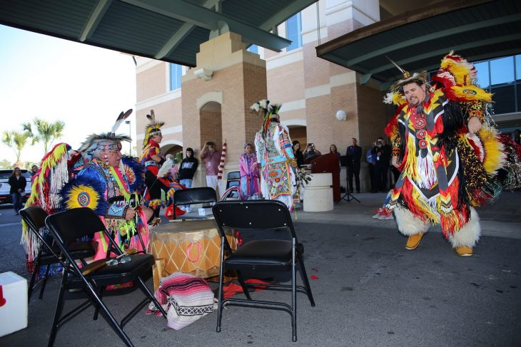 (At left) Robert Soto bangs a large drum and chants while male members of the Lipan Apache Tribe of Texas dance in front of a crowd of approximately 100 spectators during a special event held in observance of National Native American Heritage Month, which took place at the VA outpatient clinic in Harlingen, Texas, on November 16, 2018. (U.S. Department of Veterans Affairs photo by Luis H. Loza Gutierrez)