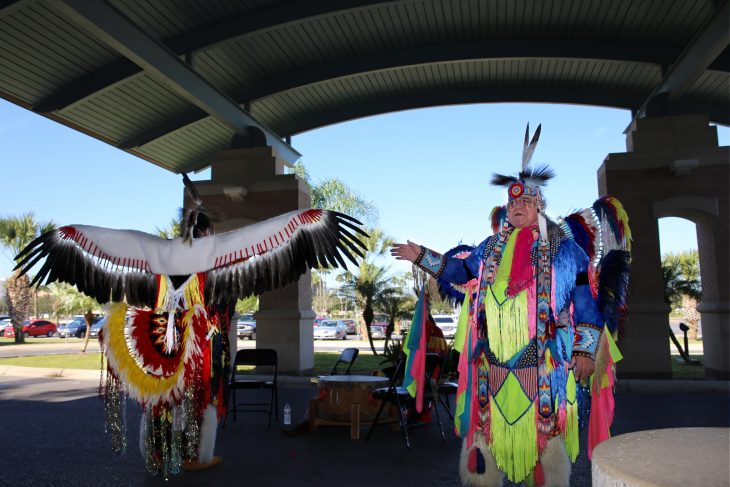 Robert Soto, the vice chairman of the Lipan Apache Tribe of Texas, explains the history and significance of the eagle feathers worn by a tribal member preparing to perform the Eagle Dance during a special event in observance of National Native American Heritage Month, which took place at the VA outpatient clinic in Harlingen, Texas, on November 16, 2018. (U.S. Department of Veterans Affairs photo by Luis H. Loza Gutierrez)