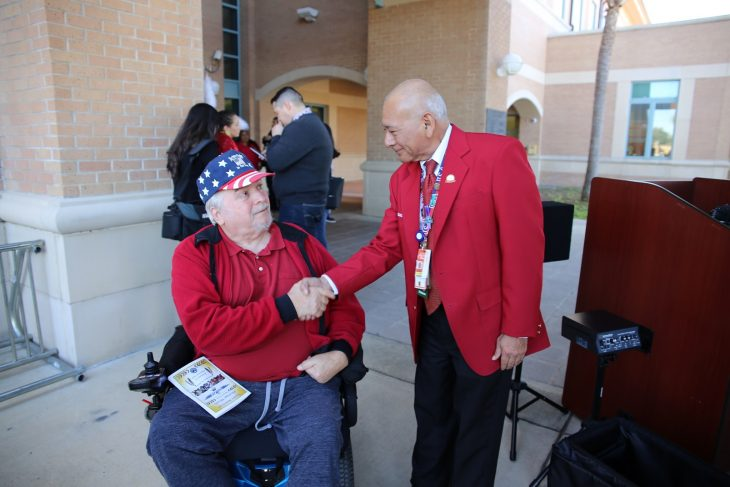(At Left) Air Force Veteran William Wilson gives a congratulatory handshake to Abel Flores, VA administrative officer for the Harlingen VA Outpatient Clinic. Flores, who is an Army Veteran and member of the Mescalero Apache Tribe was nominated by a staff member to be the VA Veteran of the Day during the observance of National Native American Heritage Month. The nomination was submitted to VAntage Point and announced publicly during a special event held in observance of National Native American Heritage Month, which took place at the VA outpatient clinic in Harlingen, Texas, on November 16, 2018. (U.S. Department of Veterans Affairs photo by Luis H. Loza Gutierrez)