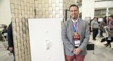 Man standing next to sculpture of giant light switch