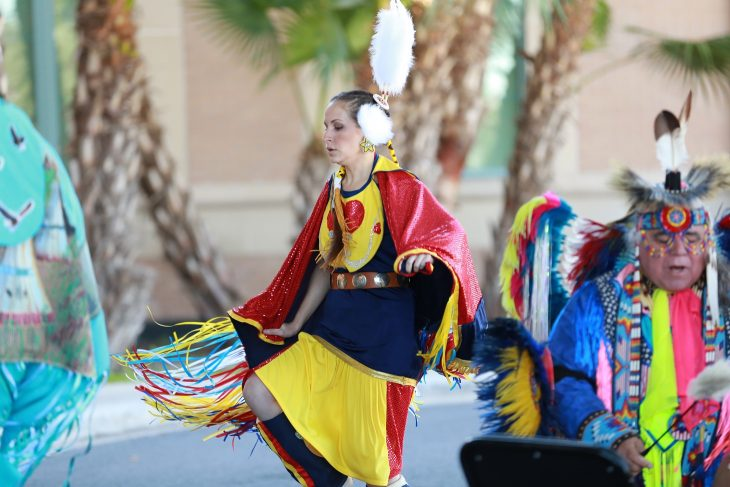 A female member of the Lipan Apache Tribe of Texas dances while other tribe members play and sing in a drum circle during a special event held in observance of National Native American Heritage Month, which took place at the VA outpatient clinic in Harlingen, Texas, on November 16, 2018. (U.S. Department of Veterans Affairs photo by Reynaldo Leal)