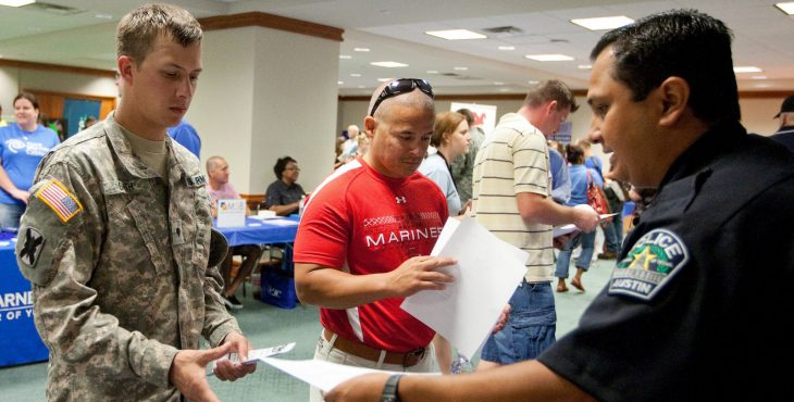 Picture shows a police officer handing a piece of paper to a service member in uniform. Other people, including Veterans in the background.