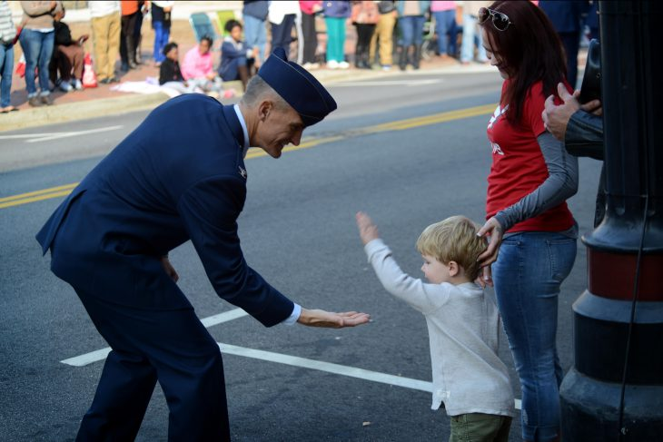 Airman giving a child a high 5