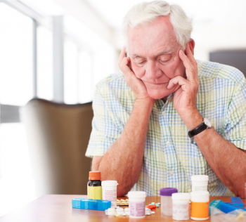 Elderly man looking at all his medications in pill bottles