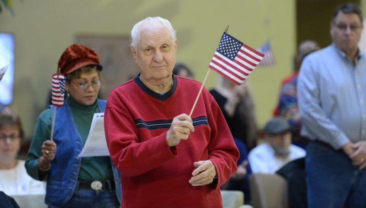 Veteran holding and waving small flag to welcome home US Troops