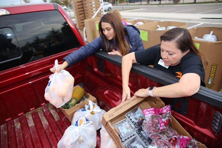 (Left to right) Food Bank of the Rio Grande Valley (RGV) employees Lorena Hertz and Yara Doyle place bags and boxes of produce into the bed of a pickup truck driven by a Veteran during the Free Produce Distribution Drive-thru held December 12, 2018, at the parking lot of the VA outpatient clinic at McAllen, Texas. (U.S. Department of Veterans Affairs photo by Luis H. Loza Gutierrez)