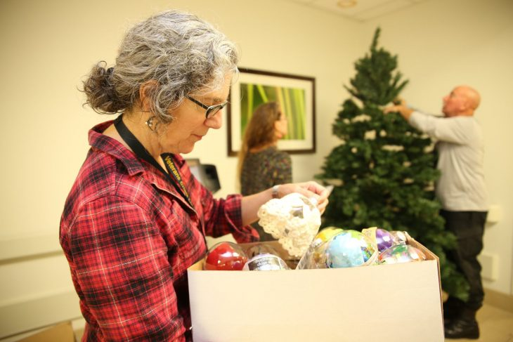 VA psychologist, Dr. Pamela Smith looks through a box containing hand-made ornaments while VA staff members and Veterans decorate a recovery holiday tree on December 11, 2018, at the VA Health Care Center at Harlingen, Texas. (U.S. Department of Veterans Affairs photo by Luis H. Loza Gutierrez)