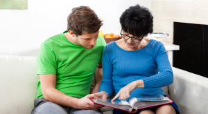 A woman and her son sitting on a sofa looking through a book.
