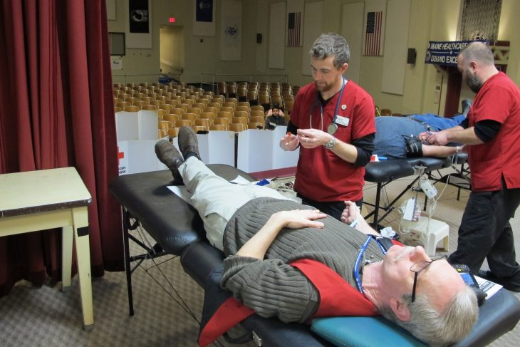 A man lies on a hospital bed giving blood