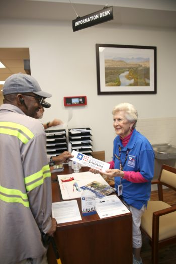 VA volunteer LaVerne Shrader helps raise awareness about suicide prevention by passing out items like the bumper sticker with the Veterans Crisis Line logo and number to a Veteran on January 16, 2019, at the VA outpatient clinic in Corpus Christi, Texas. (U.S. Department of Veterans Affairs photo by Luis H. Loza Gutierrez)