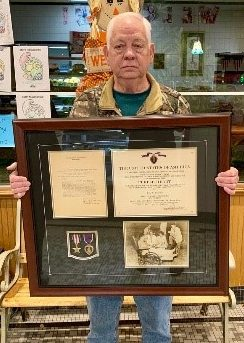 Picture shows a man holding a framed medal along with various citations and a picture.