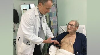 A doctor using an ultrasound device on a Veteran in bed