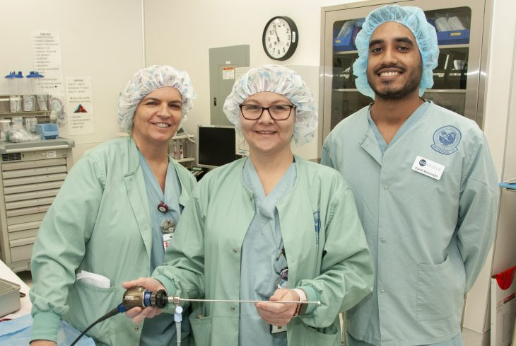 Surgical team poses for photo with the GloShield device