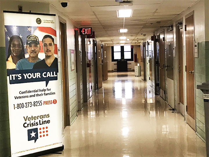 Picture shows an empty hallway with a Veterans Crisis Line poster hanging on the left hand side.