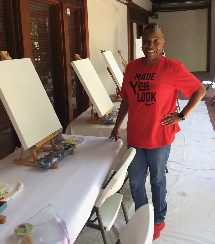 Felisa Gaffney is standing in front of tables with blank canvasses on them.