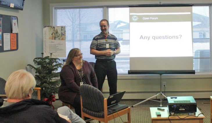Two people answering questions next to a slide screen