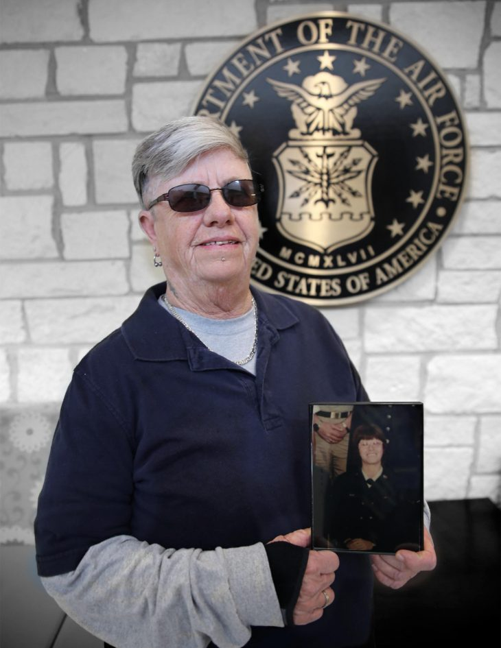 With a photo of herself in military uniform in her hands, American military Veteran Ginger Bryant poses for a portrait in front of the seal of the U.S. Air Force, located inside the main lobby of the VA's specialty clinic in Corpus Christi, Texas, on February 21, 2019.  Bryant was one of 22 women Veterans from the Corpus Christi area who participated in VA Texas Valley Coastal Bend Health Care System's (VCB) 2019 Women Veteran's Portrait Project, which is designed to recognize servicewomen during Women's History Month, a nation-wide observance that takes place in March. Bryant is a Vietnam War-Era Veteran and served in the Air Force from 1971 to 1974. She achieved the rank of airman 1st class.   The photo in Bryant's hands was captured in February 1972 during her time at Lowry Air Force Base, Colorado, where she completed technical training to become an inventory management specialist.  (VA photo illustration by Luis H. Loza Gutierrez)