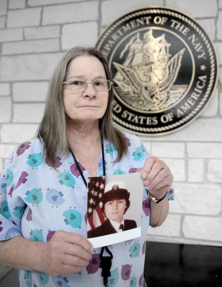 With a framed photo of herself in military uniform in her hands, American military Veteran Dawn Cherry poses for a portrait in front of the seal of the U.S. Navy, located inside the main lobby of the VA's specialty clinic in Corpus Christi, Texas, on February 22, 2019. Cherry was one of 22 women Veterans from the Corpus Christi area who participated in VA Texas Valley Coastal Bend Health Care System's (VCB) 2019 Women Veteran's Portrait Project, which is designed to recognize the service of Women Veterans from the local community during Women's History Month, a nation-wide observance that takes place in March. The former Sailor achieved the rank of petty officer 2nd class and served in the Navy for six years from 1984 to 1990.  She worked as a hospital corpsman during her enlistment. She continues to help serve her fellow Veterans by working as a medical technician at the VA in Corpus Christi. (VA photo by Luis H. Loza Gutierrez)