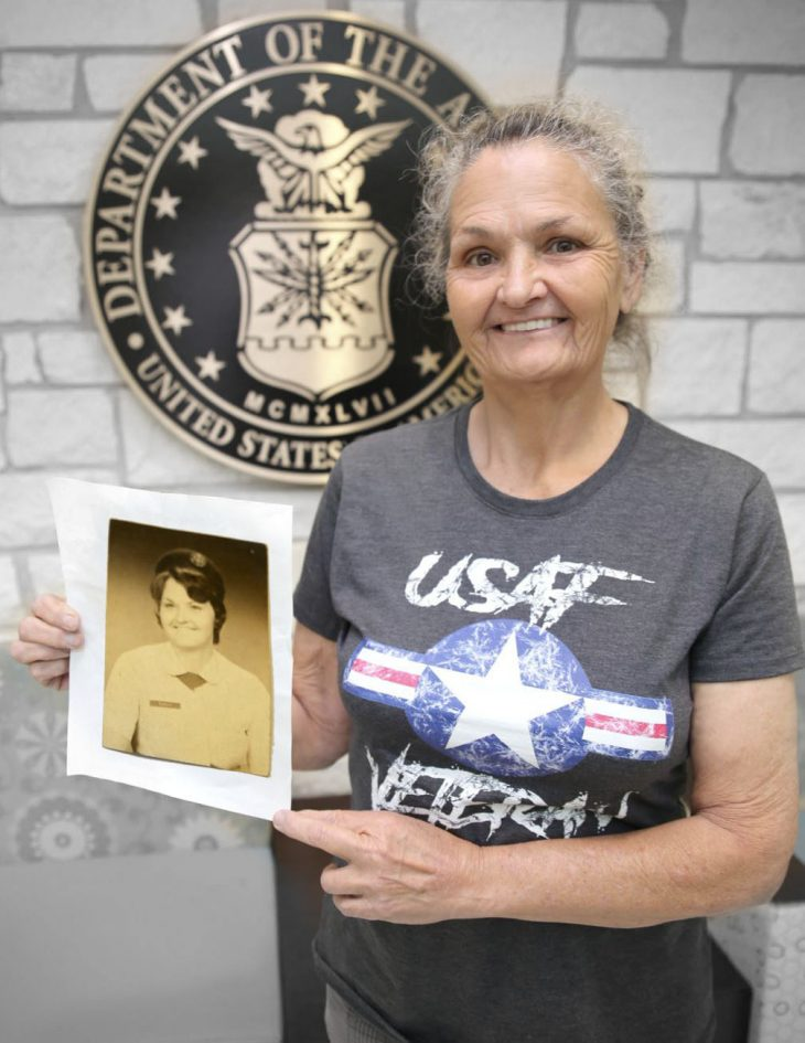With a photo of herself in military uniform in her hands, American military Veteran Linda Early poses for a portrait in front of the seal of the U.S. Air Force, located inside the main lobby of the VA's specialty clinic in Corpus Christi, Texas, on February 22, 2019.  Early was one of 22 women Veterans from the Corpus Christi area who participated in VA Texas Valley Coastal Bend Health Care System's (VCB) 2019 Women Veteran's Portrait Project, which is designed to recognize the service of Women Veterans from the local community during Women's History Month, a nation-wide observance that takes place in March.  Early is a served in the Air Force for one year as an air operations specialist. The former airman 1st class continued to serve her fellow Veterans as a civilian employee for the Department of the Navy. She amassed more than 37 years of combined federal service.   (VA photo illustration by Luis H. Loza Gutierrez)