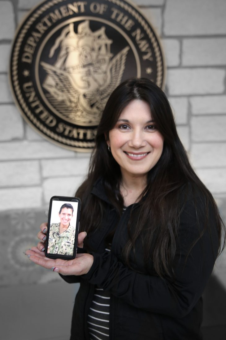 With her smart phone displaying a photo of herself in military uniform in her hands, American military Veteran Dawn Cherry poses for a portrait in front of the seal of the U.S. Navy, located inside the main lobby of the VA's specialty clinic in Corpus Christi, Texas, on February 22, 2019.  Charles was one of 22 women Veterans from the Corpus Christi area who participated in VA Texas Valley Coastal Bend Health Care System's (VCB) 2019 Women Veteran's Portrait Project, which is designed to recognize the service of Women Veterans from the local community during Women's History Month, a nation-wide observance that takes place in March. The former Sailor achieved the rank of petty officer 1st class and served in the Navy for 20 years from 1995 to 2014.  She worked as a Cox 1 which is sometimes referred to as a coxswain. As a Cox 1 the former Sailor was in charge of a small water vessel or boat. During her enlistment she conducted operations in support of Operation Iraqi Freedom.  (VA photo illustration by Luis H. Loza Gutierrez)