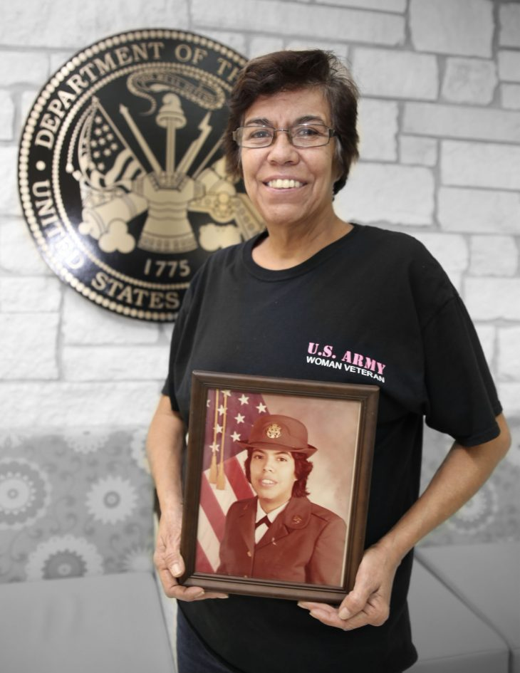 With a framed photo of herself in military uniform in her hands, American military Veteran Diana Downs poses for a portrait in front of the seal of the U.S. Army located inside the main lobby of the VA's specialty clinic in Corpus Christi, Texas, on February 22, 2019. Downs was one of 22 women Veterans from the Corpus Christi area who participated in VA Texas Valley Coastal Bend Health Care System's (VCB) 2019 Women Veteran's Portrait Project, which is designed to recognize the service of Women Veterans from the local community during Women's History Month, a nation-wide observance that takes place in March. Downs served in the Army from January 1979 to July 1982. She achieved the rank of sergeant and worked as a tactical circuit controller during her enlistment. (VA photo illustration by Luis H. Loza Gutierrez)
