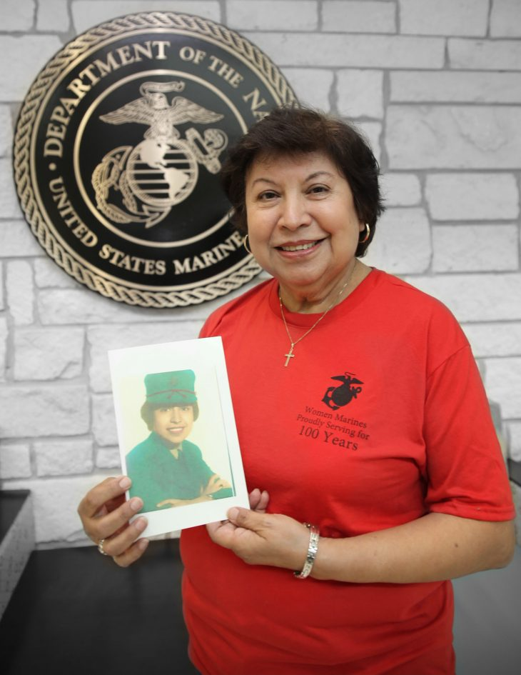 With a photo of herself in military uniform in her hands, American military Veteran Maria Elena Crowley poses for a portrait in front of the seal of the U.S. Marine Corps, located inside the main lobby of the VA's specialty clinic in Corpus Christi, Texas, on February 21, 2019. Crowley was one of 22 women Veterans from the Corpus Christi area who participated in VA Texas Valley Coastal Bend Health Care System's (VCB) 2019 Women Veteran's Portrait Project, which is designed to recognize the service of Women Veterans from the local community during Women's History Month, a nation-wide observance that takes place in March. Crowley is a Vietnam War-Era Veteran and served in the Marine Corps from 1964 to 1967. During her enlistment, the former area director for the local Women Marines Association worked as a general's writer, a legal stenographer and a staffing administrator. The photo in Crowley's hands was captured shortly after she completed basic military training.  (VA photo illustration by Luis H. Loza Gutierrez)