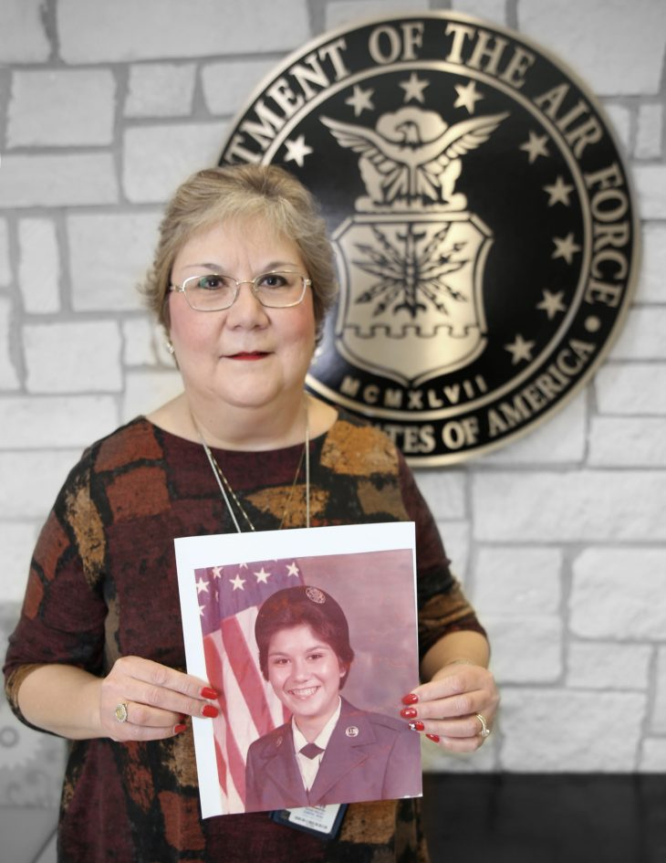 With a photo of herself in military uniform in her hands, American military Veteran JoAnn Melendez poses for a portrait in front of the seal of the U.S. Air Force, located inside the main lobby of the VA's specialty clinic in Corpus Christi, Texas, on February 22, 2019. Melendez was one of 22 women Veterans from the Corpus Christi area who participated in VA Texas Valley Coastal Bend Health Care System's (VCB) 2019 Women Veteran's Portrait Project, which is designed to recognize the service of Women Veterans from the local community during Women's History Month, a nation-wide observance that takes place in March. Melendez served four years in the Air Force from 1980 to 1984. She achieved the rank of buck sergeant and worked as a travel and finance specialist.  The photo in Melendez's hands was captured shortly after graduating basic military training at Lackland Air Force Base, Texas, in July of 1980.  (VA photo by Luis H. Loza Gutierrez)