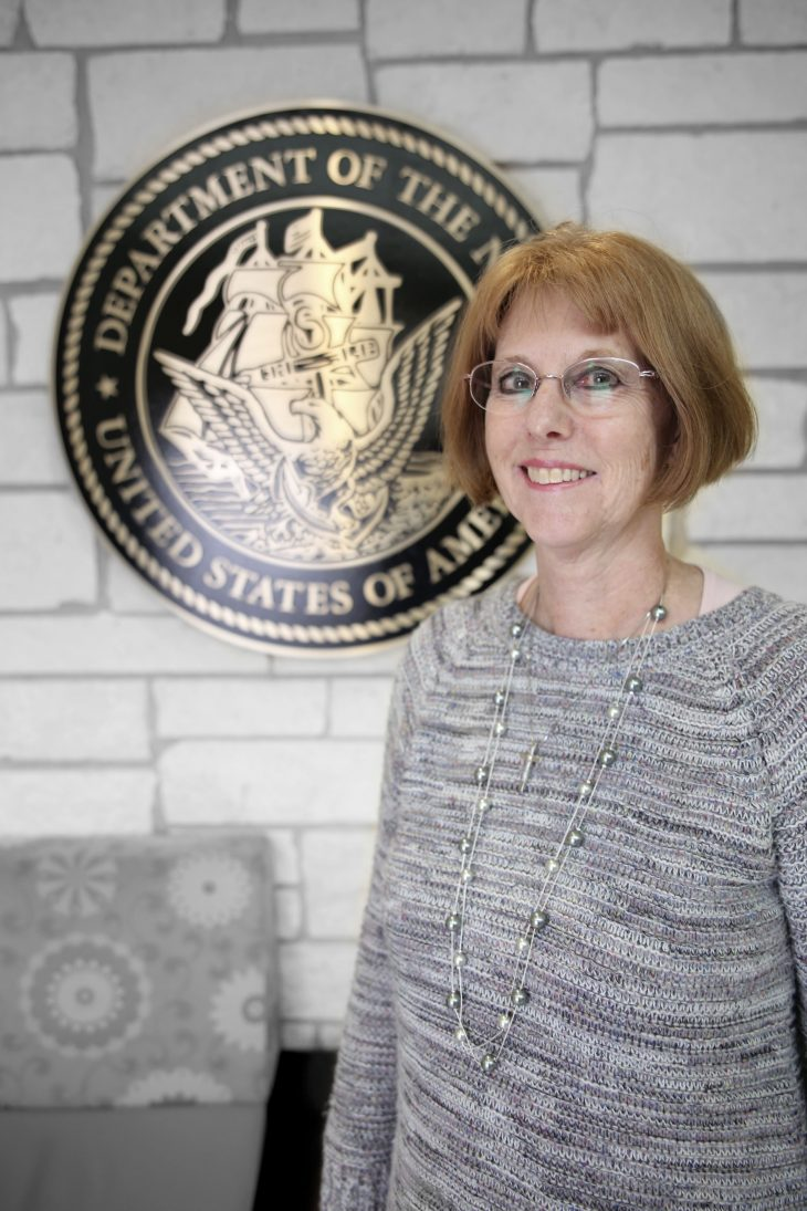 American military Veteran Christine R. Livezey poses for a portrait in front of the seal of the U.S. Navy, located inside the main lobby of the VA's specialty clinic in Corpus Christi, Texas, on February 22, 2019. Livezey was one of 22 women Veterans from the Corpus Christi area who participated in VA Texas Valley Coastal Bend Health Care System's (VCB) 2019 Women Veteran's Portrait Project, which is designed to recognize the service of Women Veterans from the local community during Women's History Month, a nation-wide observance that takes place in March. The former Sailor achieved the rank of petty officer 2nd class and served in the Navy for five years from 1985 to 1990.  She worked as a data processing specialist during her enlistment. She served aboard the U.S.S. Acadia AD-42.  (VA photo illustration by Luis H. Loza Gutierrez)