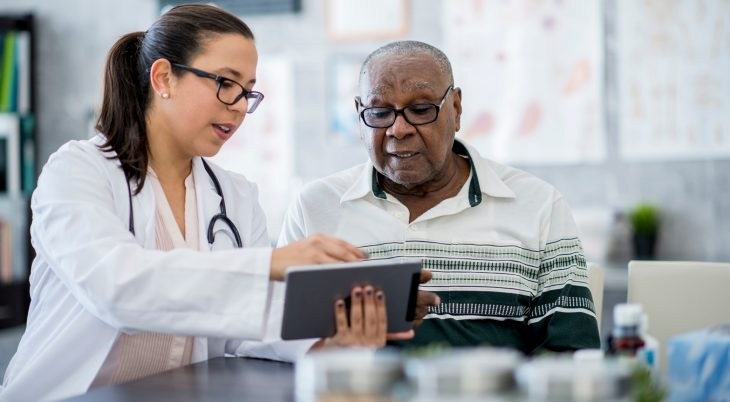 Older patient in a health care office receives medical counsel from a practitioner holding a tablet device.