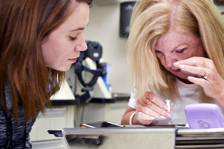 Dr. Cara Smith helps Veteran Iona Trexler insert her scleral lenses to check for fit of the lens