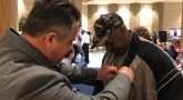 IMAGE of a VA employee pinning a commemorative pin on a Vietnam Veteran