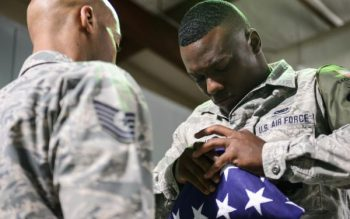 An Air Force airman folds an American flag