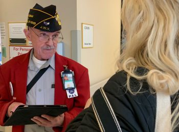 Air Force Veteran and Red Coat Ambassador Fred Piess talks with visitors at the Detroit VA.