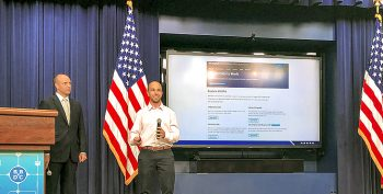 Picture shows a photo of two people giving a presentation.