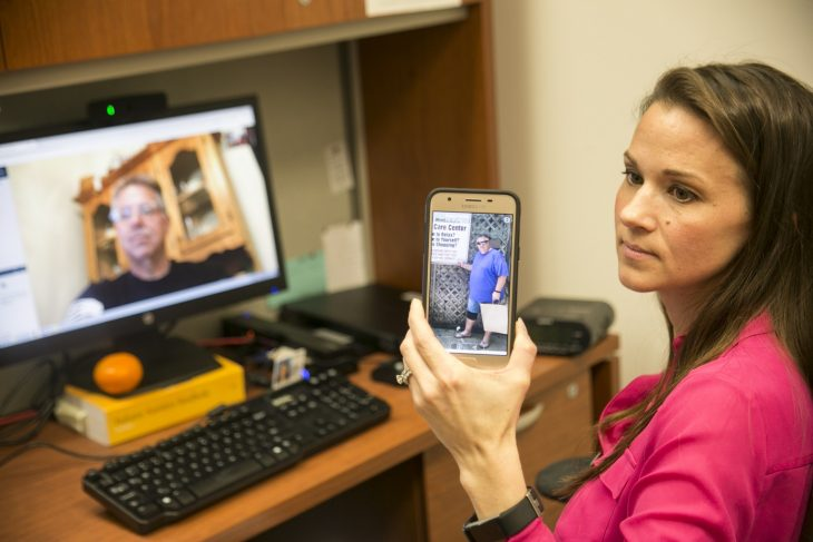 IMAGE of MOVE Program coordinator holding up a smart phone