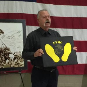 Larry Williams receives a set of yellow footprints for his support of the Dallas-Fort Worth Veterans Center.