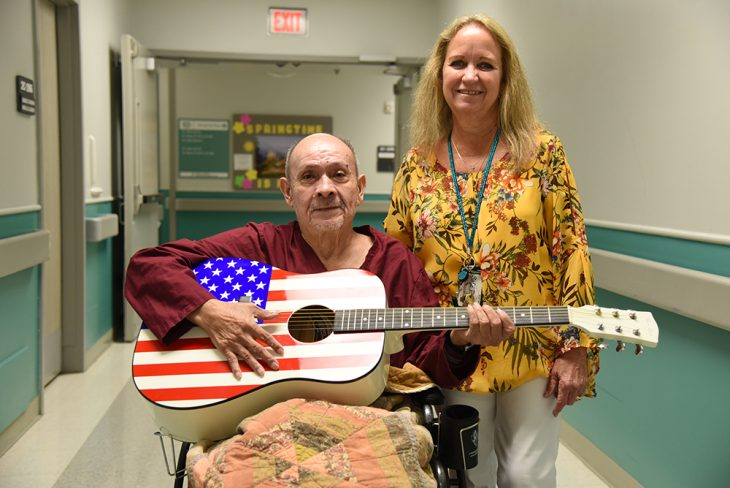 A man and his guitar and his female art therapy instructor