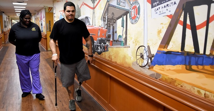 IMAGE: U.S. Army Veteran Charles Jones works with Tashenia Hunter, physical therapist, learning to walk with his new prosthetic leg. Jones is in the Amputation Specialty Program (ASP), an intense rehabilitation program requiring three hours of therapy a day.