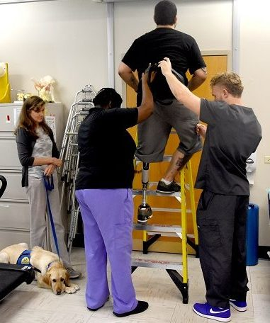IMAGE: U.S. Army Veteran Charles Jones climbs up a ladder with his new prosthetic leg doing return to work activities while in the Amputation Specialty Program (ASP), an intense rehabilitation program requiring three hours of therapy a day.