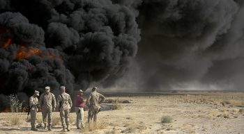 Soldiers on the ground near a smoking pit