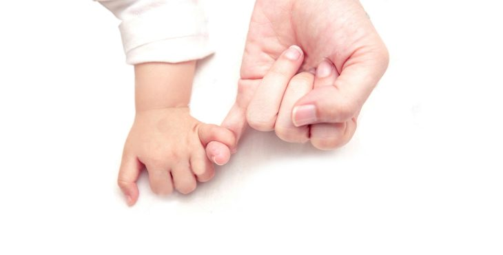 Image: baby hand holding an adult finger