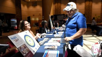 A women Veteran speaks with a VA employee at a Women's Health Week event.
