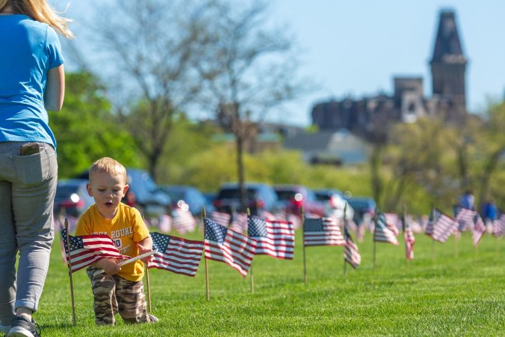 2-year-old Brooks Sansone holds a ruler marking the spot for his mother Nikki Sansone to place an American flag during the traditional flag-placing at Wood National Cemetery. More than 35,000 flags will fly at each of the Veterans interred at the cemetery in preparation of Memorial Day.